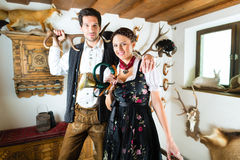 Hunter and woman in an alpine mountain hut with horn Stock Photo