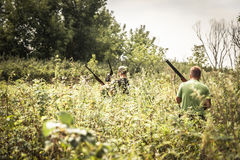 Hunters breaking through bushes during hunting season in summer day royalty free stock photography
