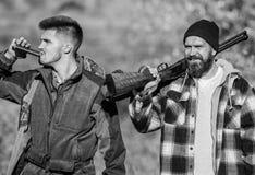 Hunters brutal poachers. Poacher partner in crime. Poaching concept. Activity for brutal men. Hunters poachers looking. For victim. Hunters with rifles in stock photography