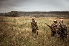 Hunters in camouflage walking through rural field during hunting season season in overcast day with moody sky stock photos