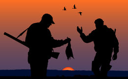 Hunters in the evening. Silhouette of two mens on the hunting Stock Images