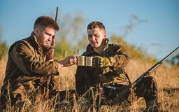 Hunters friends enjoy leisure. Hunters satisfied with catch drink warming beverage. Rest for real men concept. Hunters. With rifles relaxing in nature stock photography