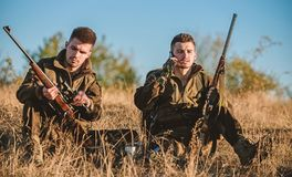 Hunters friends enjoy leisure. Rest for real men concept. Hunters with rifles relaxing in nature environment. Hunting. With friends hobby leisure. Hunters royalty free stock images