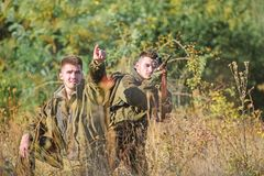 Hunters gamekeepers looking for animal or bird. Hunting with friends hobby leisure. Hobby for real men concept. Hunters. With rifles in nature environment royalty free stock photo