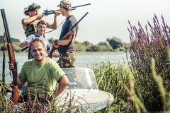 Hunters with guns in boat on river bank during hunting season among reed stock photo