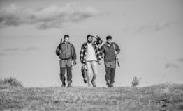 Hunters with guns walk sunny fall day. Brutal hobby. Guys gathered for hunting. Group men hunters or gamekeepers nature. Background blue sky. Men carry hunting royalty free stock photography