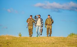 Hunters with guns walk sunny fall day. Brutal hobby. Guys gathered for hunting. Group men hunters or gamekeepers nature. Background blue sky. Men carry hunting royalty free stock photos