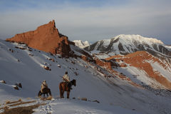 Hunters on horseback in winter in the mountains of Tien Shan Stock Photos