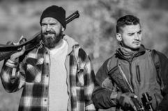 Hunters poachers looking for victim. Hunters with rifles in nature environment. Illegal hunting. Hunters brutal poachers. Poacher partner in crime. Poaching royalty free stock photo