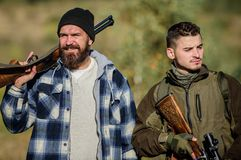 Hunters poachers looking for victim. Hunters with rifles in nature environment. Illegal hunting. Hunters brutal poachers. Poacher partner in crime. Poaching royalty free stock photography