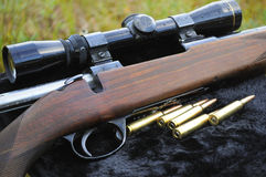 Hunters rifle. Closeup of a hunters rifle with a lens and ammo Royalty Free Stock Photography