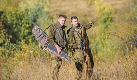 Hunters with rifles in nature environment. Poacher partner in crime. Activity for real men concept. Hunters gamekeepers. Looking for animal or bird. Illegal stock photo