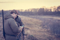 Hunters in rual field during hunting season holding smartphone Stock Image
