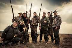 Hunters standing together against sunrise sky in rural field during hunting season. Concept for teamwork Royalty Free Stock Images