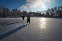 Hunters with weapons on the ice pond. Stock Photos