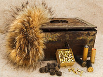 Hunting. Photo of old cartridge for hunting rifle and vintage rusty chest with fox brush against beige background stock image