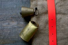 Hunting accessories for bird dog lies on a old cloth and wooden. High quality bronze bell and swiss bell for bird dog lies on an old cloth on a wodden background royalty free stock photo