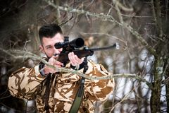 Hunting, army, military concept - sniper holding rifle and aiming at target in the forest during operation Stock Photos
