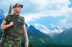 Young soldier or hunter with gun over mountains. Hunting, army, military service and people concept - young soldier, ranger or hunter with gun over mountains Stock Images