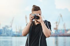 Hunting for best shots. Portrait of attractive urban photographer with vintage camera taking photos near sea, walking. Around city to picture every interesting Royalty Free Stock Images