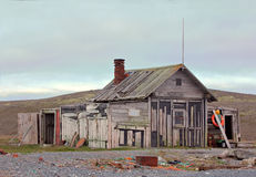 Hunting cabin on shore of the Arctic ocean. Old hunting Lodge built right on pebbly beach of North sea stock images