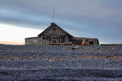 Hunting cabin on shore of the Arctic ocean. Old hunting Lodge built right on pebbly beach of North sea royalty free stock images