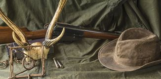 Hunting carbine, deer antlers, trap and cowboy hat Royalty Free Stock Photos