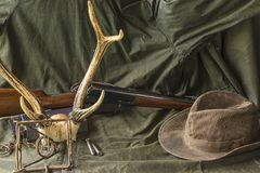 Hunting carbine, deer antlers, trap and cowboy hat Stock Photos