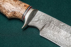 Hunting damascus steel knife handmade on a green fabric Stock Image