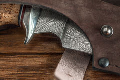 Hunting damascus steel knife handmade on a wooden background, close-up Royalty Free Stock Photos