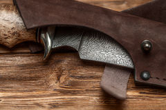 Hunting damascus steel knife handmade on a wooden background, close-up Stock Images
