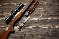 Hunting equipment on old wooden background. A gun with an optical sight, a hunting knife on a wooden background.Top view Stock Photo