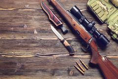 Hunting equipment on old wooden background. A gun with an optical sight, a hunting knife on a wooden background.Top view Stock Images