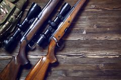 Hunting equipment on old wooden background. Hunting rifle and ammunition on a dark wooden background.Top view Stock Photos