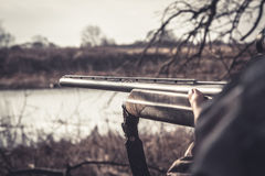 Hunting. Gun barrel ready to shot during duck hunting season on river bank in overcast day Stock Photography