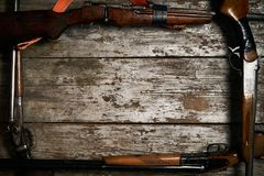 Hunting guns frame on wooden table. Background with copy space for text, top view. ollection of hunting rifles. Rifles, shotguns on wooden table background Stock Photo