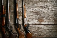Hunting guns frame on wooden table. Background with copy space for text, top view. ollection of hunting rifles. Rifles, shotguns on wooden table background Stock Photography