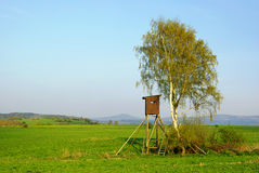 Hunting hide in countryside. Wooden hunting hide under tree in green countryside Stock Images