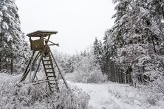 Hunting hide in winter. Wooden hunting hide covered with snow in a winter forest stock image