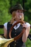 Hunting horn's girl musician playing Royalty Free Stock Images