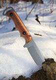 Hunting knife. Stuck in a snowy stump royalty free stock photo