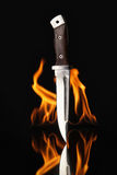 Hunting knife with fire on a black background Royalty Free Stock Photos