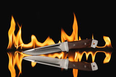 Hunting knife with fire on a black background Royalty Free Stock Photography