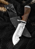 Hunting knife with a fishing net on a wooden table. Hunting knife with a fishing net on a wooden table Stock Photo