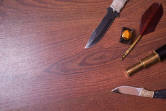 Hunting knife, fountain pen and ink, spyglass on wooden background Royalty Free Stock Images