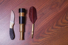 Hunting knife, fountain pen. Spyglass on wooden background Stock Photography