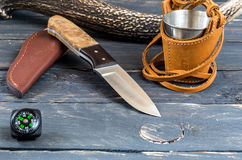 Hunting knife, a glass and a compass. Dark background stock photo