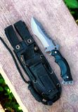Hunting knife. Large hunting knife on wood outdoors royalty free stock photography
