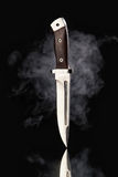Hunting knife with smoke on a black background Stock Photos