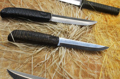 Hunting knives on a background of wood and hay Stock Photography